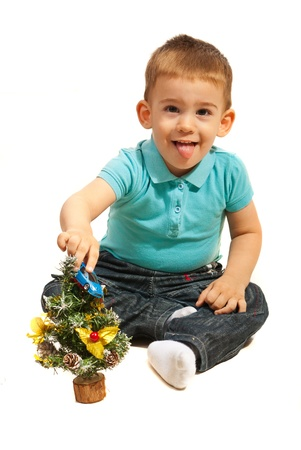 Cute toddler boy with tongue out playing with a toy car and a Xmas tress isolated on white background photo