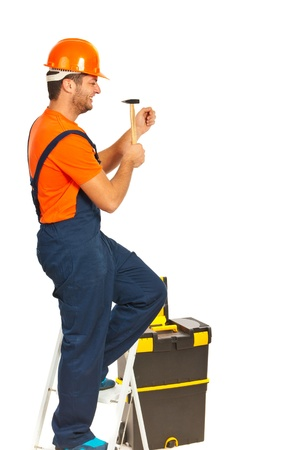 step ladder: Builder man standing on step ladder and working with a hammer isolated on white background