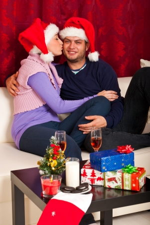 Loving Christmas couple kissing and sitting on couch together photo
