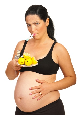flu shot: Sad pregnant woman with thermometer  having fever and being cold  holding lemons and pills isolated onw hite background