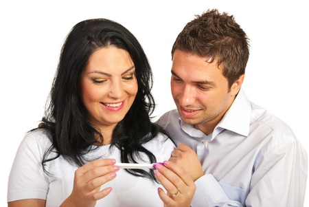 Happy couple looking at positive pregnancy test isolated on white background Stock Photo