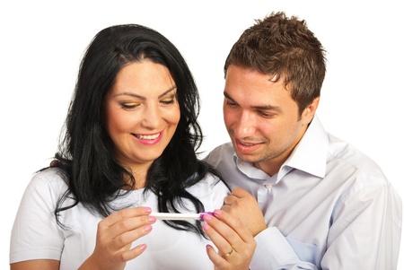 prueba de embarazo: Pareja feliz mirando prueba de embarazo positiva aislada en el fondo blanco
