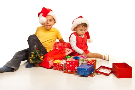 Kids sitting on florr with many Christmas gifts around them  photo