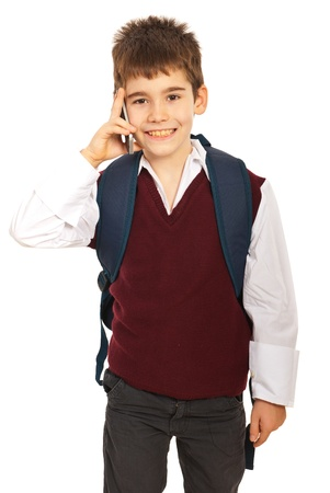 kids wear: Cheerful schoolboy talking by phone mobile isolated on white background