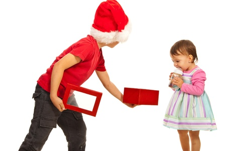 Boy showing to a toddler an open Christmas box and the girl being amazed isolated on white background photo