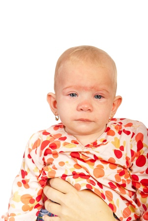 the infancy: Crying baby girl with tears in her mother hands isolated on white background