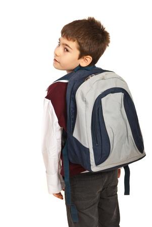 Student jongen met tas terug te kijken over de schouder geïsoleerd op witte achtergrond Stockfoto