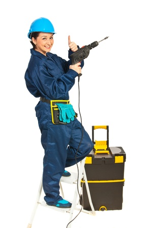 Successful driller woman standing on step ladder isolated on white background photo