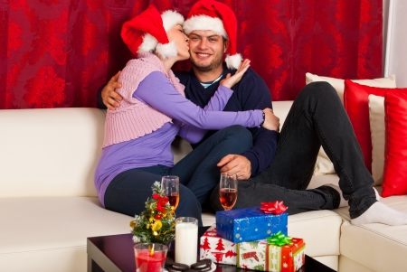 Kissing happy Chrostmas couple sitting on couch home photo