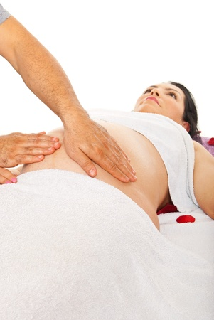therapeutic massage: Pregnant woman receiving belly massage isolated on white background