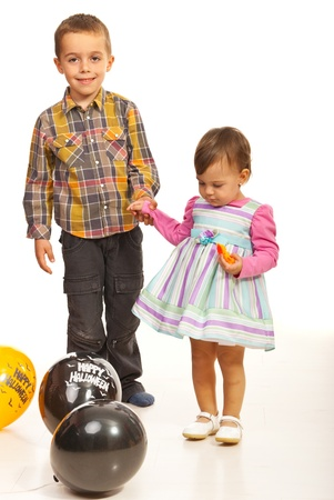 Walking kids holding  their hands among Halloween balloons photo