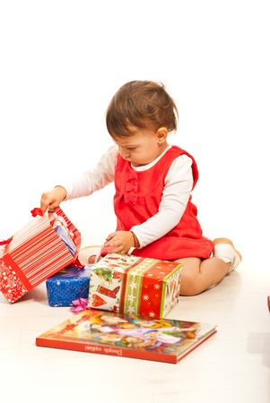 baby open present: Toddler girl opening presents and sitting on floor home Stock Photo
