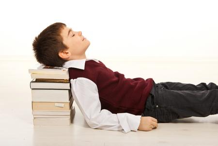 Student jongen slapen met het hoofd op stapel boeken naar huis Stockfoto