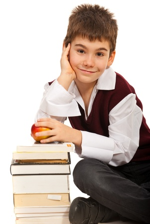 Smiling  student boy  holding apple and resting hand on books isolated on white background Stock Photo - 16300575