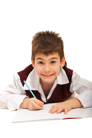 Smiling schoolboy doing homework isolated on white background photo
