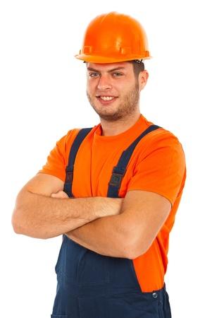 mani incrociate: Allegro uomo lavoratore costruttore con le braccia incrociate isolato su sfondo bianco Archivio Fotografico