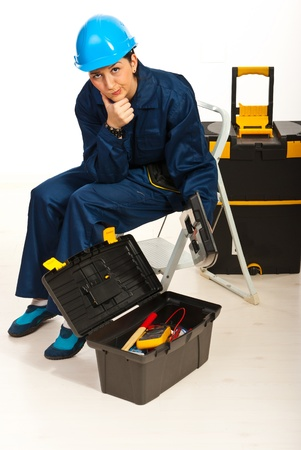 step ladder: Confused workers woman sitting on step ladder  with tool box open