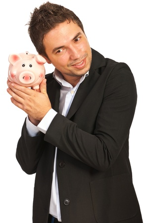Happy executive man listening to piggy bank isolated on white background photo