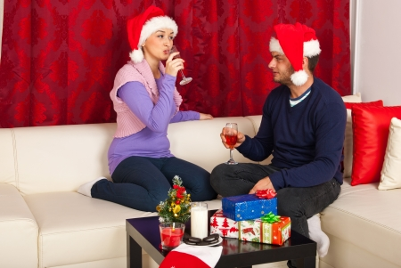 Couple  celebrating with wine Christmas night  and sitting together on couch home photo
