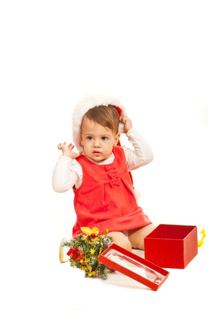 baby open present: Toddler girl with tree and Christmas gift on the floor isolated on white background