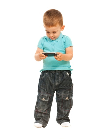 sens: Toddler boy holding phone mobileand sending sms message isolated on white background Stock Photo