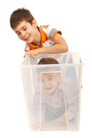 Big brother laughing while his little bro being in a transparent box isolated on white background photo