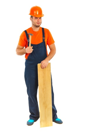 Full length of repairman with hammer and wood plank isolated on white background photo
