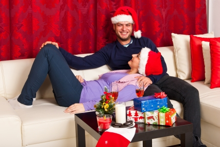 Couple having happy conversation  and sitting on sofa home in Christmas night isolated on white background photo