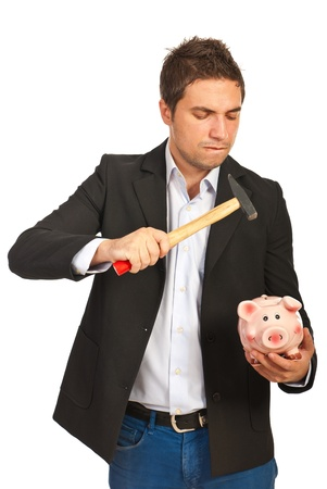 Furious business man broke a piggy bank with a hammer isolated on white background photo