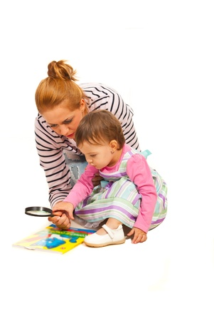 Mother teaching her daughter to read and holding magnifier isolated on white background photo