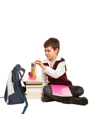 Student boy choice a pencil and prepare to make homework and sitting on the floor photo