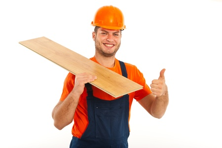 Happy builder man carrying  wood plank and giving thumb up isolated on white background photo