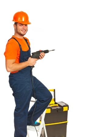 stepladder: Happy repairman with drill on stepladder isolated on white background Stock Photo
