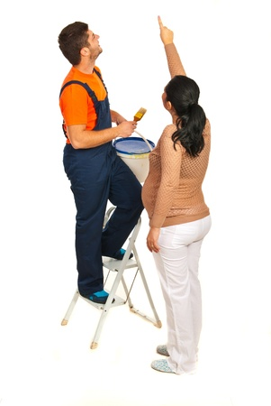 Pregnant woman shoing to a painter man where to paint on the wall isolated on white background photo