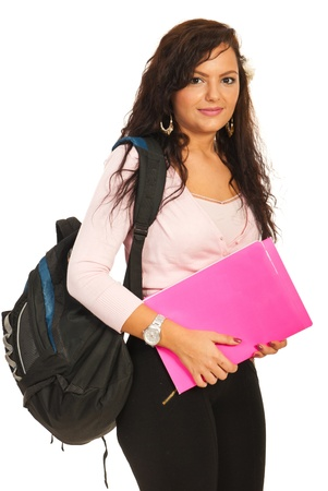studio shots: Smiling student woman holding pink notebooks and bag on her shoulder isolated on white background