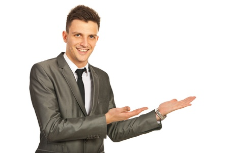 welcoming: Happy business man making presentation with both hands to copy space isolated on white background