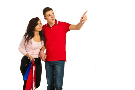 Amazed couple at shopping looking away and man pointing to copy space isolated on white background photo