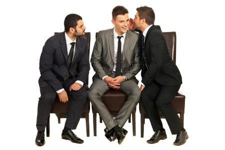 Business man vertelt een geheim aan een collega, terwijl andere proberen te luisteren en zitten allemaal op chiars geïsoleerd op witte achtergrond