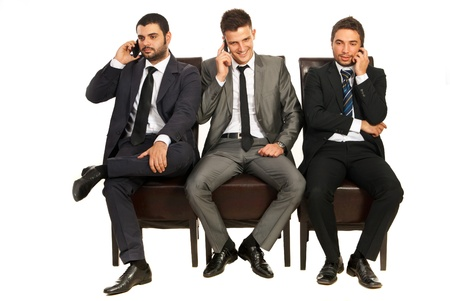 Drie business mannen zitten op stoelen in een lijn en het spreken door telefoons mobiele geïsoleerd op witte achtergrond Stockfoto
