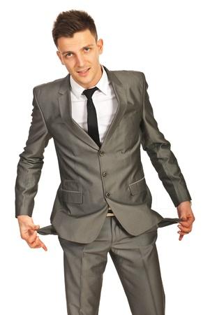 hombre pobre: Hombre de negocios que muestra los bolsillos del pantalón vacíos aislados en fondo blanco Foto de archivo