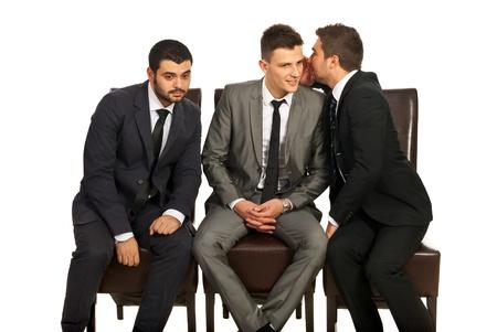 Hombre de negocios que comparten un secreto a su colega y el otro tratando de escuchar aisladas sobre fondo blanco Foto de archivo