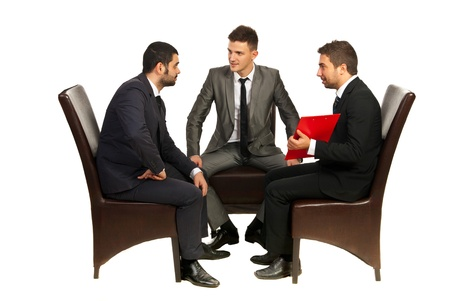 people sitting on chair: Meeting of three business men sitting on chairs and having conversation isolated on white background