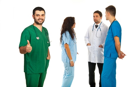 Doctor man giving thumb up in front of his team of doctors isolated on white background photo