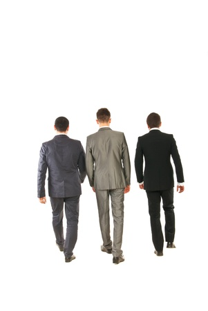 Back of three business men walking isolated on white background photo