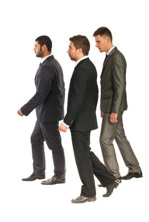 hombre de perfil: Perfil de tres hombres de negocios a pie al trabajo aislado en el fondo blanco