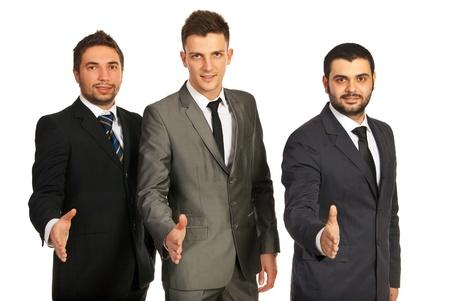 manos estrechadas: Equipo de tres hombres de negocios de pie en una l�nea y dando apretones de manos aisladas en fondo blanco