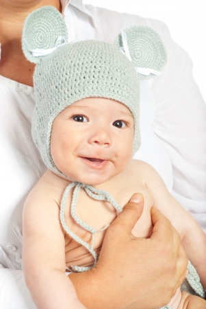 Happy newborn baby boy with crochet mouse cap in mother hands photo