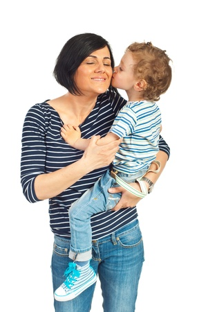 Toddler standing in his mother arms and kissing her cheek isolated on white background photo