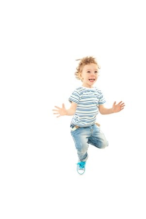 Jumping happy toddler boy with arms open isolated on white background photo