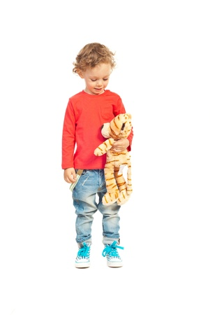 Toddler boy talking with tiger toy isolated on white background photo
